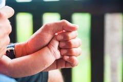 Closeup av faderhanden som rymmer den lilla nyfödda sonhanden Arkivbild