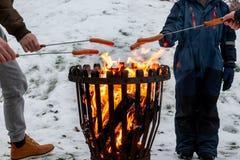 Closeup av familjen på en lägereld som grillar varmkorvmat Utomhus- plats för vintersnö arkivbilder