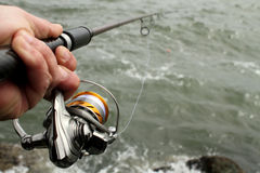 Closeup av fiskerullen i hand Arkivbilder