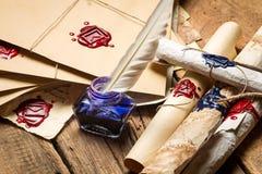 Closeup av forntida snirklar och det gamla kuvertet med den blåa bläckhornen Royaltyfri Fotografi