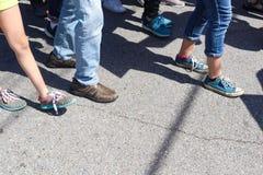 Closeup av fot och ben - folk som går på den spruckna trottoaren med olika skor och flåsanden arkivbild