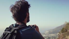 Closeup av fotvandraren med kikare som står mot himmel lager videofilmer