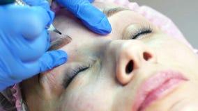 Closeup av framsidan för ung kvinna som får ögonbrynet som microblading i skönhetsalong arkivfilmer