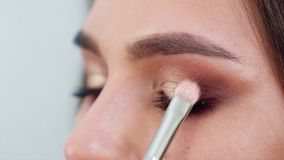 Closeup av framsidan för ung kvinna som får yrkesmässig makeup i ultrarapid arkivfilmer