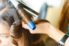 Closeup av frisören som gör utforma för en festlig afton av bröllopfrisyrkvinnan med långt svart hår royaltyfri foto