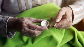 Closeup av gamla händer som rymmer en ask med preventivpillerar arkivbild