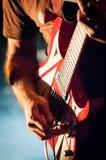Closeup av gitarristhanden under konsert, avsiktligt kornigt a Arkivbilder