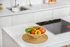Closeup av grönsaker i bunken i modernt vitt kök med induktionsmatlagningvärmeapparaten och vask på bakgrund arkivbild