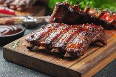 Closeup av grisköttstöd som grillas med BBQ-sås och caramelizeds i honung Smakligt mellanmål till öl på ett träbräde för att spar fotografering för bildbyråer