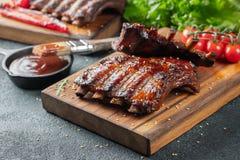 Closeup av grisköttstöd som grillas med BBQ-sås och caramelizeds i honung Smakligt mellanmål till öl på ett träbräde för att spar arkivbilder