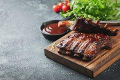 Closeup av grisköttstöd som grillas med BBQ-sås och caramelizeds i honung Smakligt mellanmål till öl på ett träbräde för att spar royaltyfria bilder