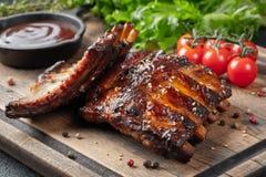 Closeup av grisköttstöd som grillas med BBQ-sås och caramelizeds i honung Smakligt mellanmål till öl på ett träbräde för att spar royaltyfri foto