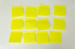Closeup av 12 gula klibbiga anmärkningar för mellanrum på det vita brädet Fotografering för Bildbyråer