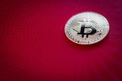 Closeup av guld- bitcoin på röd bakgrund Fotografering för Bildbyråer