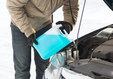 Closeup av hällande frostskyddsvätska för man in i vattenbehållare Royaltyfria Foton