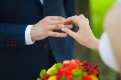 Closeup av händer av brud- oigenkännliga par med vigselringar bruden rymmer bröllopbuketten av blommor Arkivbild