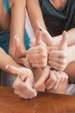 Closeup av händer av tre Caucasian kvinnlig som visar upp tummar in Royaltyfri Bild