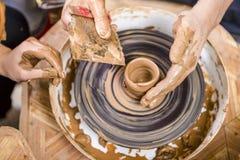 Closeup av händer av den manliga keramikern som undervisar hans kvinnliga lärling royaltyfri foto