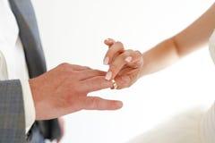 Closeup av händer för en brud som och brudgumisoleras över en vit bakgrund arkivfoto