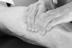 Closeup av händer av kiropraktorn, fysioterapeut som gör kalvmus royaltyfri fotografi