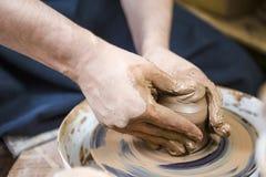 Closeup av händer av manligt keramikerarbete med Clay Lump på keramikers hjul royaltyfria bilder