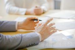 Closeup av händer med finansiella diagram på affärsmötet i kontoret Arkivfoto