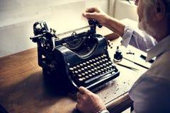 Closeup av händer som ändrar papper på tappningskrivmaskinen arkivfoto