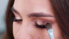 Closeup av händer som applicerar ögonskuggor till ögonlock för ung kvinna i ultrarapid stock video