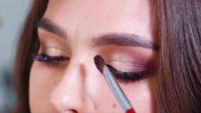 Closeup av händer som applicerar skinande ögonskuggor till ögonlock för ung kvinna i ultrarapid arkivfilmer