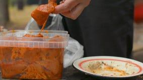 Closeup av händer som klipper kött för shaslikBBQ-kebab med en kniv som förbereder ett mål lager videofilmer
