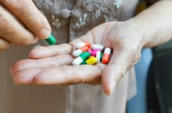 Closeup av hållande preventivpillerar för en äldre hand royaltyfri bild