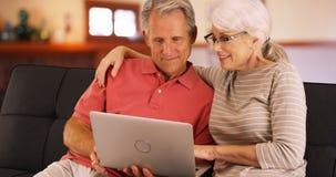 Closeup av höga par genom att använda bärbara datorn hemma royaltyfria bilder