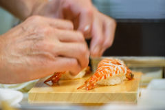 Closeup av handen av den japanska sushikocken Arkivbild