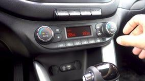 Closeup av handen som justerar luftkonditioneringsapparatknappen i bilen Man som använder det betingande systemet för billuft stock video
