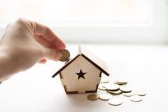 Closeup av handen som sätter myntet i spargrisen för trähus på vit bakgrund placera text Sparande pengar, bostadslån, intecknar,  arkivfoton
