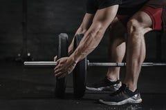 Closeup av idrottsman nen som förbereder sig för lyftande vikt på crossfitidrottshallen Skivstångmagnesiaskydd Övande funktionell arkivbilder