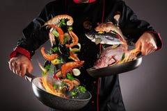 Closeup av kocken som kastar den havsfrukt och fisken royaltyfri foto
