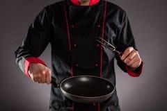 Closeup av kocken som rymmer den tomma stekpannan och gaffeln royaltyfria bilder