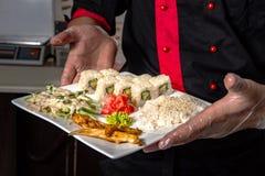 Closeup av kockhänder som rullar upp sushiinställning på plattan på kök royaltyfri fotografi