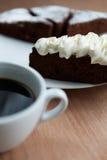 Closeup av koppen av svart kaffe och kakan Arkivbilder