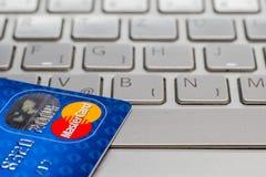 Closeup av kreditkorten MasterCard På bärbar datortangentbordet Fotografering för Bildbyråer