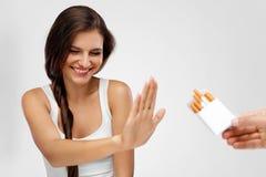 Closeup av kvinnan som ger upp som röker cigaretter band för mått för äpplebegreppshälsa Arkivbild