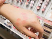 Closeup av läppstift för kvinnahandprovning med olika färger royaltyfri fotografi