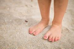 Closeup av lite ben och fot för flicka` som s går på sanden av stranden med havsvattnet i bakgrundssommaren royaltyfri fotografi