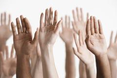 Closeup av lyftta multietniska händer Arkivbilder