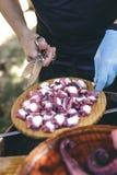 Closeup av mänskliga händer som förbereder den lagade mat plattan av galicianstil Arkivbilder