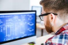 Closeup av mannen i exponeringsglas som gör ritningar på datoren Arkivfoton