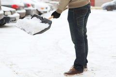 Closeup av mannen som skyfflar snö från körbanan Arkivfoto