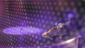 Closeup av nålvisaren på snurrvinylrekordet, discjockey som spelar musik på nattklubben lager videofilmer