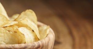 Closeup av naturliga potatischiper med svartpeppar i träbunke på tabellen arkivfoto